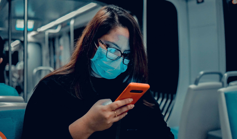 woman wearing mask on phone